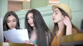 Female friends sitting in cafeteria and discuss project. Group of three girlfriend talk about fashion design sitting on the couch. In bistro stock video footage