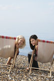Female Friends Sitting On Deckchairs At Beach Royalty Free Stock Images