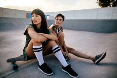 Female friends sitting relaxed at skate park. Two young women sitting on long board and looking away. Female friends sitting relaxed at skate park Stock Photos