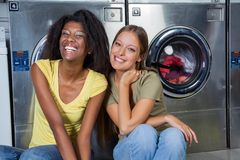 Female Friends Sitting Together At Laundry Stock Image