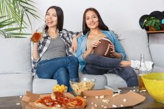 Female friends sport fans watching match holding rugby ball stock photo