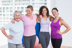 Female friends standing arms around in fitness studio Royalty Free Stock Image