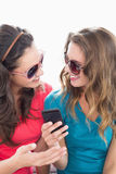 Female friends in sunglasses reading text message Stock Image