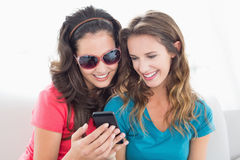 Female friends in sunglasses reading text message Royalty Free Stock Photo