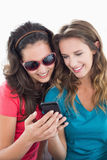 Female friends in sunglasses reading text message Royalty Free Stock Images