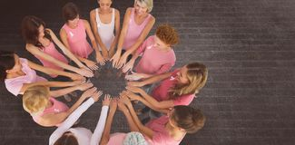 Composite image of female friends supporting breast cancer awareness Stock Images