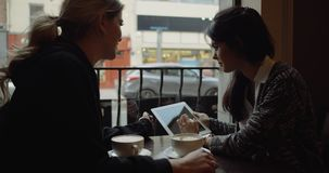 Female friends with tablet computer in cafe. 4k. Female friends with tablet computer in cafe. Slow motion. Red Epic stock video
