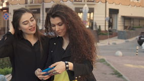 Female friends take selfie outdoors. Two pretty female friends taking selfie outdoors at the city. Attractive young women photographing themselves against stock video