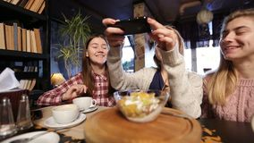 Female friends taking food picture with smartphone stock footage