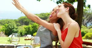 Female friends taking a selfie with mobile phone 4k. Female friends taking a selfie with mobile phone in outdoor restaurant 4k stock footage
