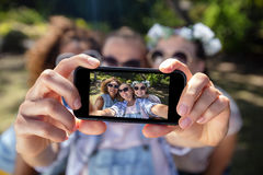 Female friends taking selfie with mobile phone. In park Royalty Free Stock Image