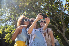 Female friends taking selfie with mobile phone. In park Stock Images