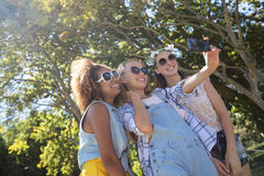 Female friends taking selfie with mobile phone. In park Stock Photo