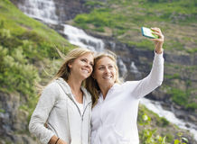 Female Friends taking selfie at a mountain waterfall Royalty Free Stock Photography