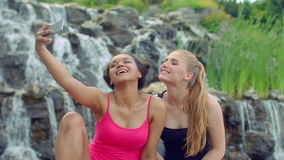 Female friends taking selfie near waterfall. Multiracial girls taking photo. With phone in park. Young women taking selfie photo. Cheerful girls posing and stock footage