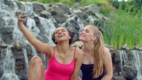 Female friends taking selfie near waterfall. Multiracial girls taking photo stock footage