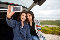 Female friends taking a selfie while on a roadtrip together Stock Images