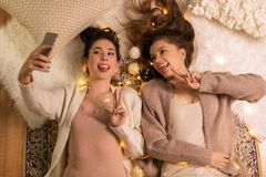 Female friends taking selfie by smartphone at home Royalty Free Stock Image