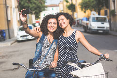 Female friends taking a selfie with their bicycles. Royalty Free Stock Images
