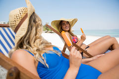 Female friends talking while sitting with popsicles on deck chair Stock Image
