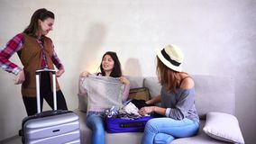 Cute girls going trip and preparing suitcases on couch in afternoon room. Female friends together collect gray and blue suitcases, add up all necessary things stock video
