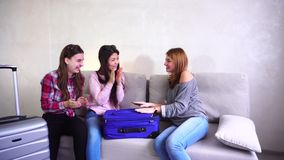 Cute girls going trip and preparing suitcases on couch in afternoon room. Female friends together collect large gray and blue suitcases, add up all necessary stock video footage