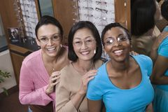 Female Friends Trying On Glasses At Optometrist Stock Photo