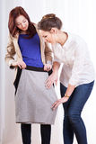 Female friends trying on pencil skirt Stock Photography