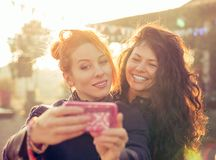 Female friends two women taking selfie having fun during weekend getaway. Outdoors Stock Images