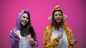 Female friends in unicorn and giraffe pajamas dancing, carnival party, fun time. Stock footage stock video