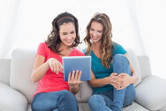 Female friends using digital tablet in the living room Royalty Free Stock Photos