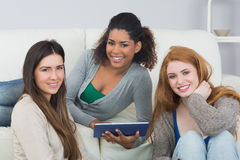 Female friends using digital tablet together at home Royalty Free Stock Photos