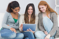 Female friends using digital tablet together on sofa Royalty Free Stock Images