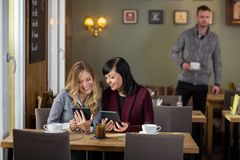 Female Friends Using Digital Tablets At Cafe Royalty Free Stock Photo
