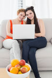 Female friends using laptop together at home. Portrait of relaxed young female friends using laptop together on sofa at home Royalty Free Stock Photography