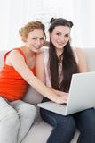 Female friends using laptop together at home. Portrait of young female friends using laptop together on sofa at home Stock Images