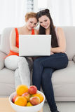 Female friends using laptop together at home Stock Image