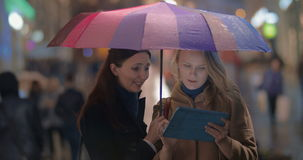 Female friends using touch pad on rainy evening in stock footage