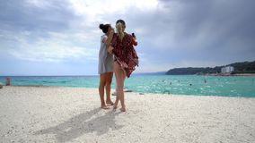 female friends on vacation taking selfies on the beach with a smart phone royalty free stock photography