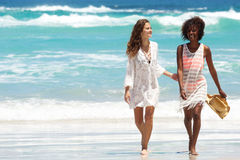 Female friends walking barefoot by the water on a beach. Full body portrait of two female friends walking barefoot by the water on a beach Royalty Free Stock Photos