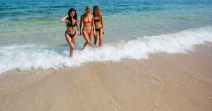 Female friends walking out of the sea water Stock Photo