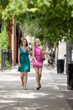 Female Friends Walking On Sidewalk Stock Photo