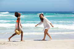Female friends walking and smiling at the beach Royalty Free Stock Images