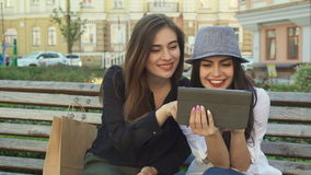 Female friends watch something on the tablet outdoors. Two pretty female friends watching something on the tablet outdoors. Attractive brunette teenager in gray stock video footage