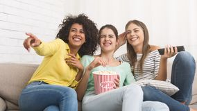 Female friends watching film and eating popcorn stock photography