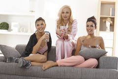 Female friends watching tv in pyjamas. Female friends watching romantic movie at home on tv, all in pyjamas Royalty Free Stock Images