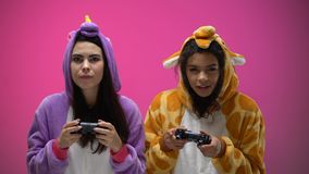 Female friends wearing giraffe and unicorn pajamas playing videogame, having fun. Stock footage stock video footage