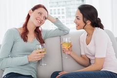 Female friends with wine glasses chatting on sofa at home Stock Image