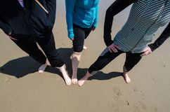 Three women friends pose with their feet in the sand at the beach. Female friendship concept, footprints on a sunny day stock image