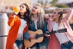 Female friendship. Creative pastime outdoors. Happy birthday party with live music Royalty Free Stock Photography